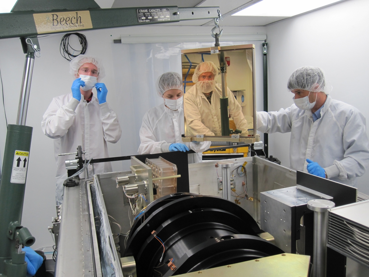 A photo of four SDSS-III scientists working on the APOGEE spectrograph.  Left to right: Garrett Ebelke (Apache Point Observatory), Gail Zasowski (The Ohio State University), Steven Majewski (University of Virginia) and John Wilson (University of Virginia). Majewski is actually standing across the room; he appears here as a reflection in a mirror that was being installed in the spectrograph.  Image credit: Dan Long (Apache Point Observatory)