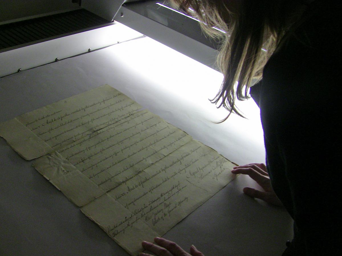 University Library System Associate Katrina Milbrodt scans a page of the 1787 charter.